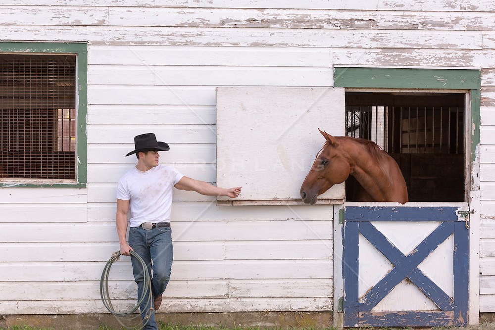 hot cowboy leaning against a barn with a horse