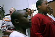 Tykym, 18, (back left), Donovan, 17 (back centre) and Michael, 17, (back right), members of the Hells Most Wanted, a Christian Hip Hop group, are singing behind two young member of the Hip Hop Church Choir, Darious Bryan, 9, (left front) and Ivan Bryan, 12, during a Mass Service at the Hip Hop Church in Harlem, New York, NY., on Thursday, July 21, 2006. A new growing phenomenon in the United States, and in particular in its most multiethnic city, New York, the Hip Hop Church is the meeting point between Hip Hop and Christianity, a place where ?God? is worshipped not according to religious dogmatisms and rules, but where the ?Holy Spirit? is celebrated by the community through young, unique, passionate Hip Hop lyrics. Its mission is to present the Christian Gospel in a setting that appeals to both, those individuals who are confessed Christians, as well as those who are not regularly attending traditional Services, while helping many youngsters from underprivileged neighbourhoods to feel part of a community, to make them feel loved and to help them not to give up when problems arise. The Hip Hop Church is not only forward-thinking but it also has an important impact where life at times can be difficult and deceiving, and where young people can be easily influenced for the worst purposes. At the Hip Hop Church, members are encouraged to sing, dance and express themselves in any way that the ?Spirit of God? moves them. Honours to students who have overcome adversity, community leaders, church leaders and some of the unsung pioneers of Hip Hop are common at this Church. Here, Hip Hop is the culture, while Jesus is the centre. Services are being mainly in Harlem, where many African Americans live; although the Hip Hop Church is not exclusive and people from any ethnic group are happily accepted and involved with as much enthusiasm. Rev. Ferguson, one of its pioneer founders, has developed ?Hip-Hop Homiletics?, a preaching and worship technique designed to reach the child