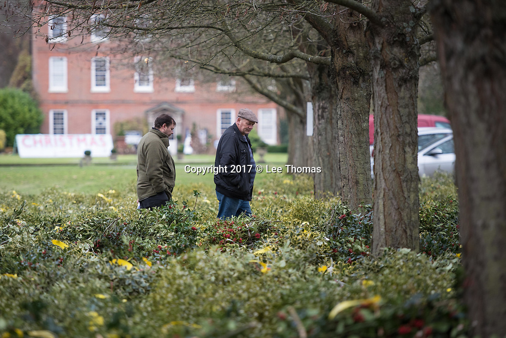 Burford House Garden Stores, Tenbury Wells, Worcestershire, UK. 5th December 2017. Buyers flock to Burford House in Tenbury Wells to take part in the annual mistletoe, wreaths, holly and Christmas tree auctions. Pictured: Buyers inspect the mistletoe with Burford House in the background. // Lee Thomas, Tel. 07784142973. Email: leepthomas@gmail.com  www.leept.co.uk (0000635435)