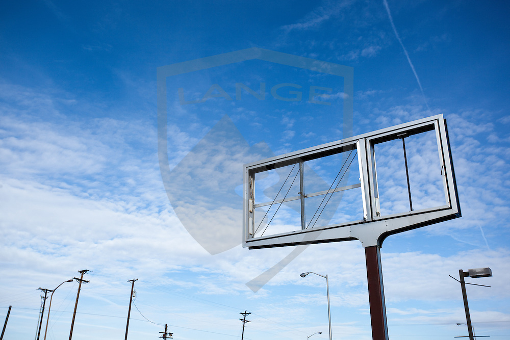 an empty sign with phone poles and light poles contrasts the cloud filled new mexico sky.  albuquerque.