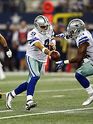 Dallas Cowboys quarterback Tony Romo (9) looks to hand off the ball to Dallas Cowboys running back Joseph Randle (21) during the NFL week 6 football game against the Washington Redskins on Sunday, Oct. 13, 2013 in Arlington, Texas. The Cowboys won the game 31-16. ©Paul Anthony Spinelli