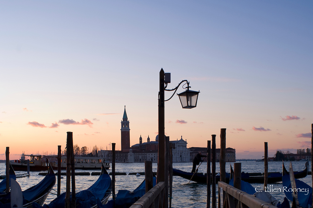 Gondolas at sunrise and San Giorgio Maggiore in silhouette in the background;<br /> Venice, Italy