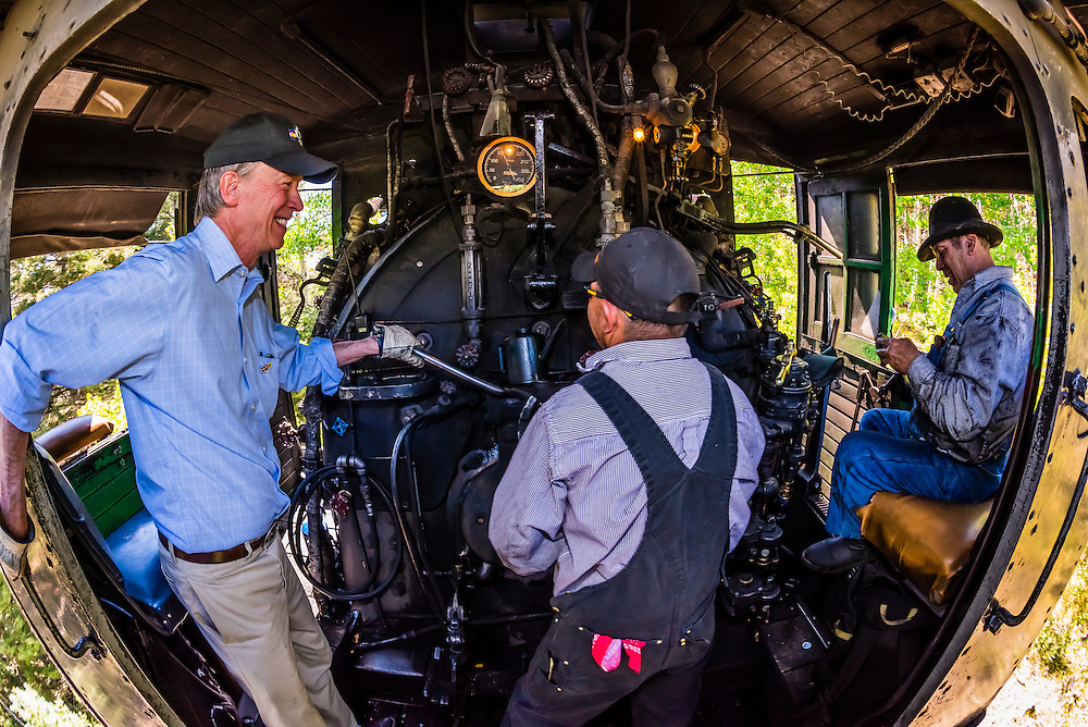 Colorado Governor John Hickenlooper riding in the steam locomotive with the train engineer and fireman during a visit to the Cumbres & Toltec Scenic Railroad from Antonito to Osier, Colorado during peak autumn color. The Cumbres & Toltec Scenic Railroad has been jointly owned by the States of Colorado and New Mexico since 1970 when it was purchased from the Denver and Rio Grande Western Railway, which was going to scrap the line. The train makes a 64 mile run between Antonito, Colorado and Chama, New Mexico. The railroad is the highest and longest narrow gauge steam railroad in the United States with a track length of 64 miles. The train traverses the border between Colorado and New Mexico, crossing back and forth between the two states 11 times. The narrow gauge track is 3 feet wide. It runs over 10,015 ft (3,053 m) Cumbres Pass.