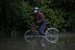 © Licensed to London News Pictures. 22/11/2016. Rotherham, UK. A cyclist struggles to ride through a flooded road in Rotherham, South Yorkshire, after a river broke it's banks last night. Storm Angus has brought heavy wind and rain to much of the UK this week with flooding seen all over. Photo credit : Ian Hinchliffe/LNP