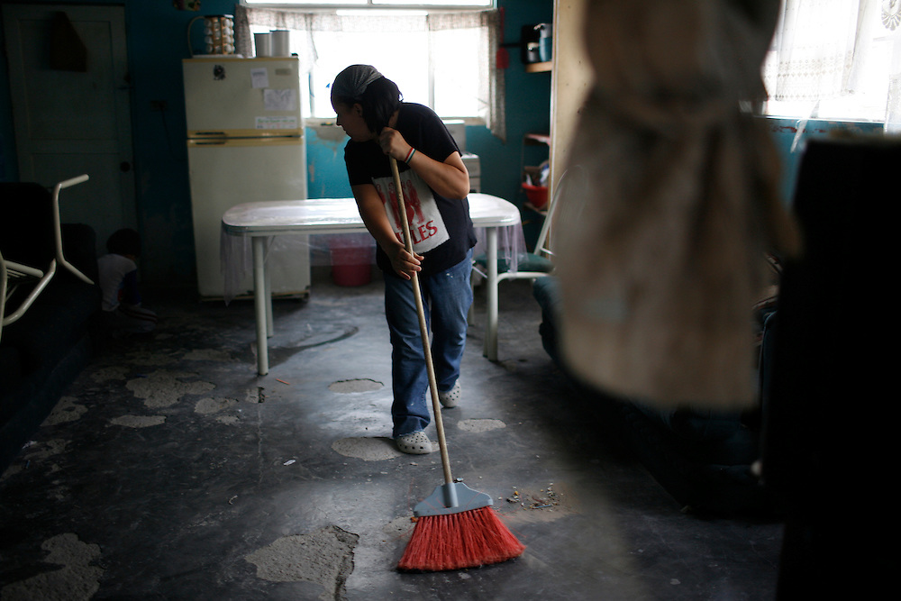 Lidia de la Torres Vazquez sweeps her house in the Diaz Ordaz colonia in Ciudad Juarez, Chihuahua Mexico on April 28, 2010.