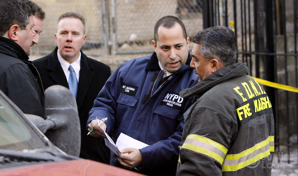 Police and fire officials stand outside of a house where 9 people were killed, 8 of them children, in an overnight fire in the Bronx, New York on Thursday 08 March 2007.