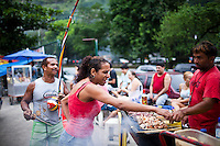 A food vender grills meat skewers at the entrance of Rocinha, in Rio de Janeiro, Brazil, on Friday, Feb. 1, 2013. The man to the left holds instruments played in capoeira. The community of Rocinha, Latin America's largest favela with an unofficial population of about 250,000 residents. Pacification and police presence have made most of the area safer for both residents and visitors.