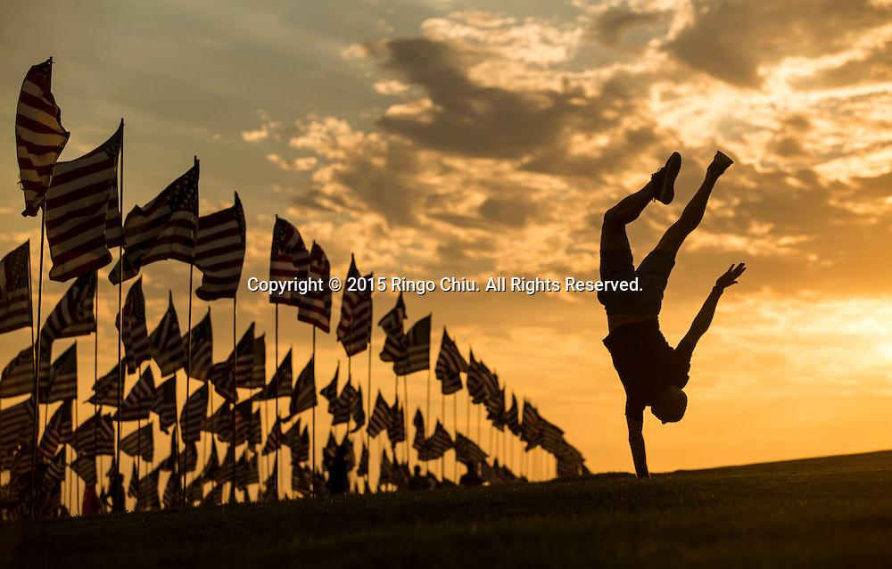 9月10日,在美国加利福尼亚州洛杉矶的马里布,一名男子倒立在旗帜旁边。当天,在美国&ldquo;9&middot;11&rdquo;事件十四周年前夕,佩珀代因大学的学生和教职员工在学校草坪上插起约3000面美国国旗,纪念&ldquo;9&middot;11&rdquo;事件遇难者。新华社发(赵汉荣摄)<br /> A man handstands aside of amongst 3,000 US flags are displayed at Pepperdine University to mark the 14th anniversary of the 9/11 terror attack, September 10, 2015 in Los Angeles, California, the United States. (Xinhua/Zhao Hanrong)Photo by Ringo Chiu/PHOTOFORMULA.com)