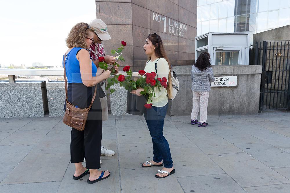 """© Licensed to London News Pictures. 11/06/2017. LONDON, UK.  Red roses are handed to Londoners and tourists on London Bridge. 1,000 red roses with messages of """"love and solidarity"""" were given to passers by on London Bridge today.  Photo credit: Vickie Flores/LNP"""