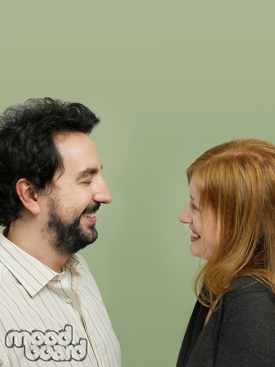 Mid adult woman and man looking in eyes profile