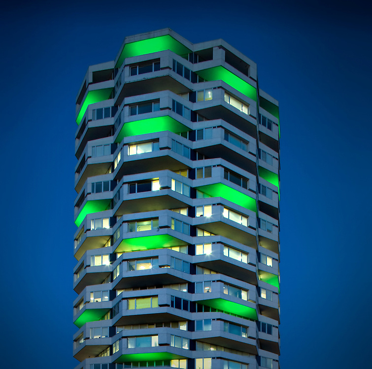 circular East Croydon office exterior at night with green lights on