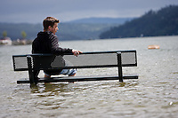 JEROME A. POLLOS/Press..Matt Jordan finds out how cold the water in Lake Coeur d'Alene is after taking a bet of $9 to walk out into the flood waters and sit on a submerged bench Wednesday.