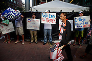 Supporters of GOP presidential candidate Mitt Romney stand in silence with signs outside Time Warner Cable Arena during the 2012 Democratic National Convention on Thursday, September 6, 2012 in Charlotte, NC.