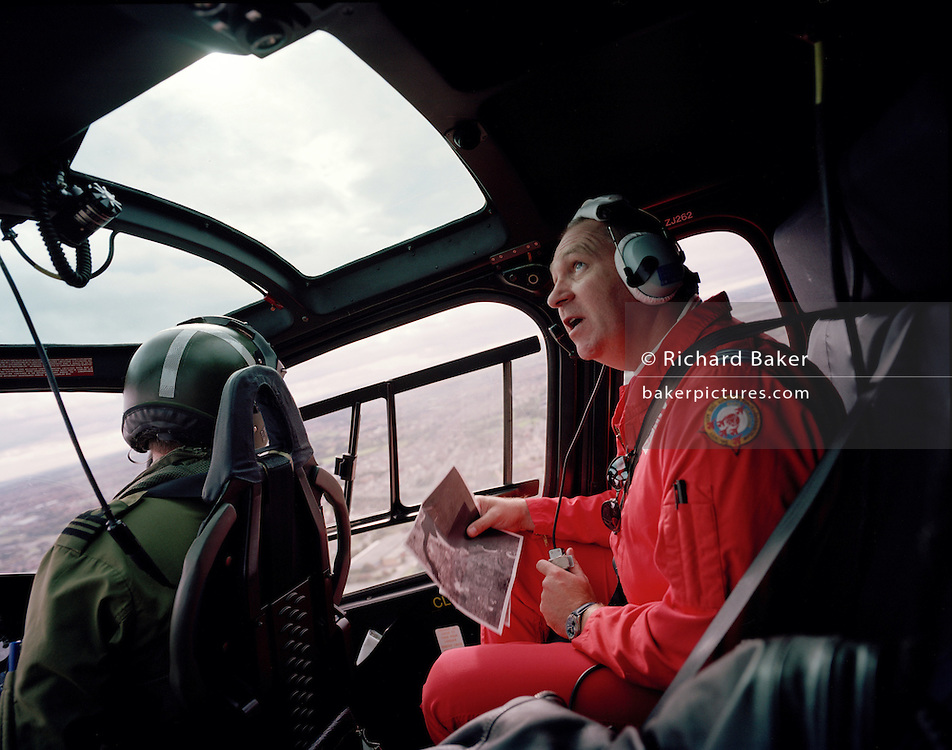 Ground commentator of the Red Arrows, Britain's RAF aerobatic team checks local cloud base during taxi ride by helicopter.