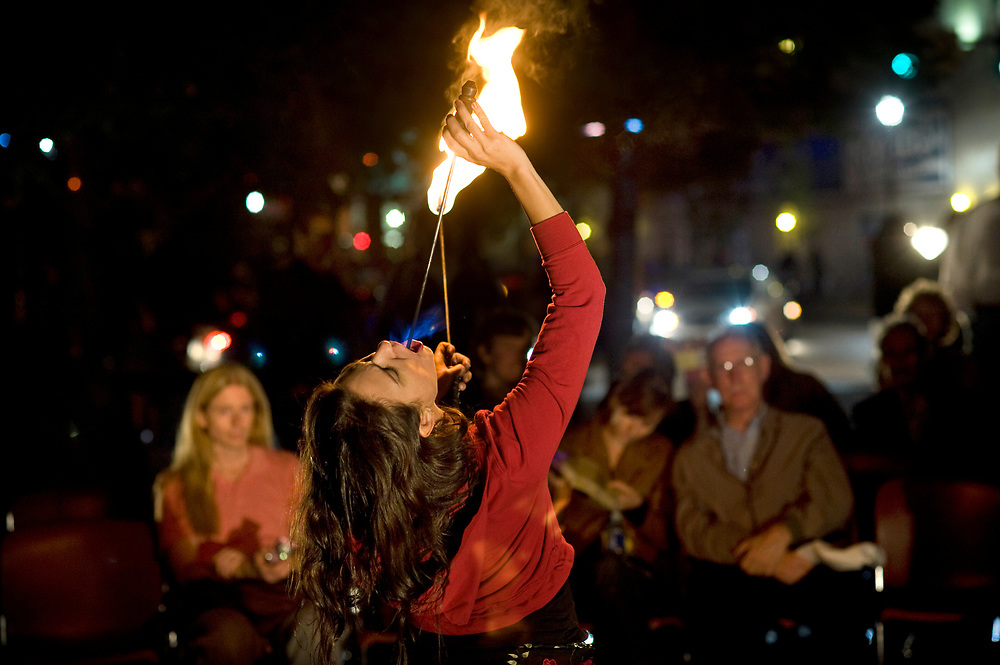 Kristin Ward, of the Middle Eastern theatrical dance group Moquette Volante, entertains attendees by eating fire at Katz Plaza during Pittsburgh Cultural Trust Fall Gallery Crawl in downtown Pittsburgh