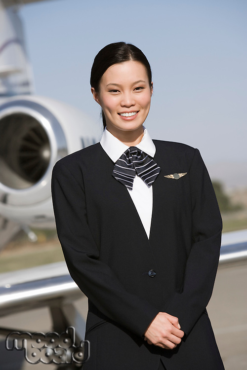 Portrait of Asian mid-adult flight attendant in front of airplane.