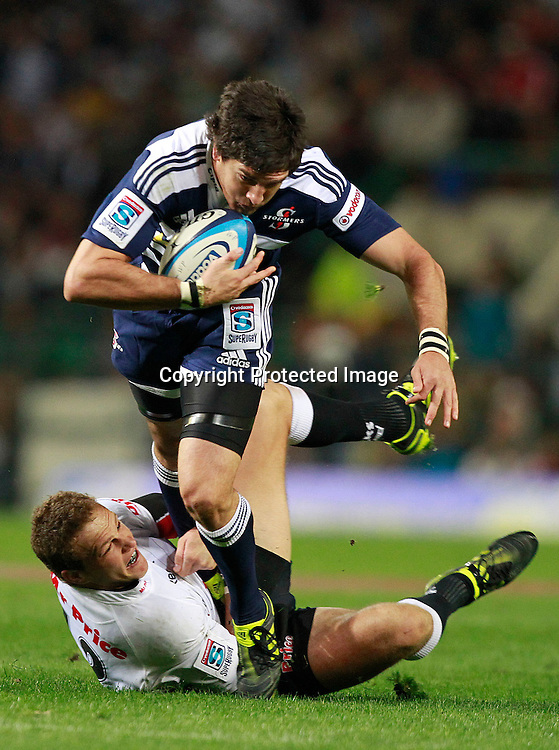 Stormers centre Jaque Fourie (R) breaks through a tackle from Sharks centre Meyer Bosman (L) during their Super Rugby match in Cape Town, South Africa 30 April 2011
