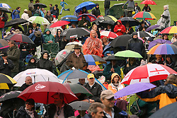 © Licensed to London News Pictures. 30/06/12. Glastonbury, UK. People shelter under umbrellas at the Orchestra in the Field Event held at Glastonbury Abbey this weekend in Somerset as a torrential downpour hit on Saturday night. Photo credit : Jason Bryant/LNP
