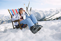 Female skier sitting on deckchair in mountains