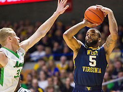Dec 17, 2015; Charleston, WV, USA; West Virginia Mountaineers guard Jaysean Paige (5) shoots a three pointer over Marshall Thundering Herd guard Austin Loop (35) during the first half at the Charleston Civic Center . Mandatory Credit: Ben Queen-USA TODAY Sports