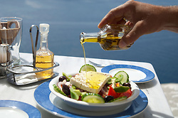 detail of a man's hand pouring oil on a greek salad at an outdoor restaurant  in Greece