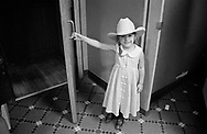 A littl girl holds the door in the rest room of a line dancing club in Nashville. Tennessee, USA