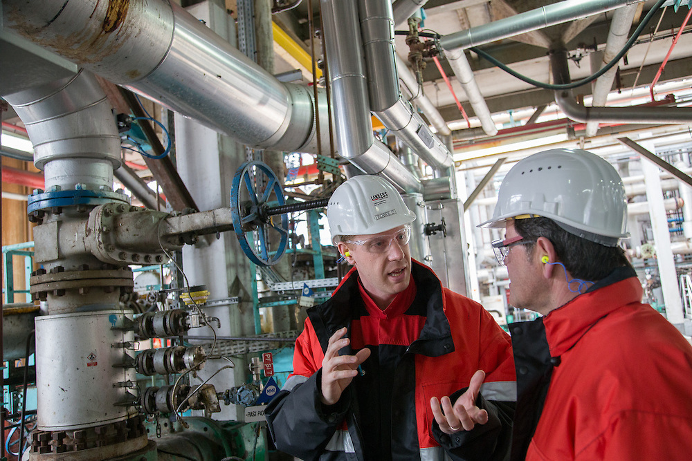 Engineers converse at the Lanxess plant for high performance rubber at the Port Jerome industrial estate, Seine Maritime, France<br /> Client: Lanxess