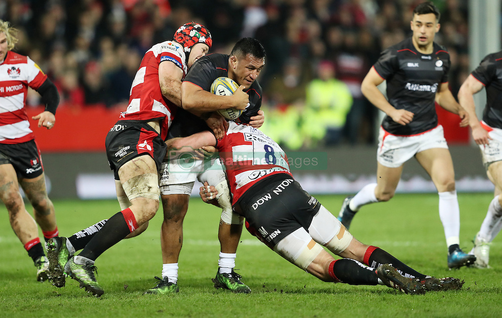 Saracens Mako Vunipola is tackled by Gloucester's Tom Savage and Ben Morgan during the Aviva Premiership match at the Kingsholm Stadium, Gloucester.