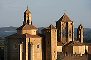 High angle view of steeple and roofs of the Cistercian abbey, Monestir de Poblet, 1151, with a strip on landscape in the distance,  Vimbodi, Catalonia, Spain, pictured on May 21, 2006, in the morning. The Monastery of Poblet belongs to the Cistercian Order and was founded by French monks. Originally, Cistercian architecture, like the rules of the order, was frugal. But continuous additions  including late Gothic and Baroque, eventually made Poblet one of the largest monasteries in Spain which was later used as a fortress and royal palace. It was closed in 1835 by the Spanish State but refounded in 1940 by Italian Cistercians. It is a UNESCO World Heritage Site. Picture by Manuel Cohen.