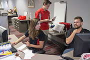 Monica Nezzer and Patrick Arite at their desks inside the Student Support Center where they work when not giving tours. Standing behind is coworker Alexander Gordon. Nezzer and Arite are students at the University of New Mexico and are working 15-30 hours per week giving campus tours in order to help put themselves through college. (Steven St. John for NPR)