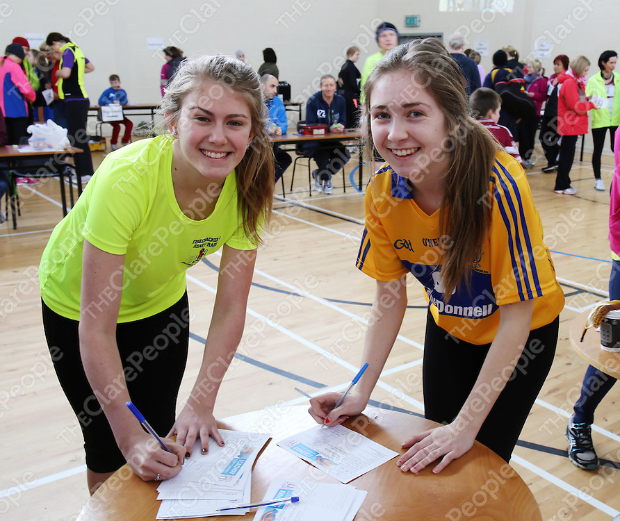 8/3/14  Derbhela Murphy and Emily Williams register at the start of the Hurley Hoey 10km run which was held at the Doora / Barefield GAA grounds on the Gurteen Road on Saturday. Pic Tony Grehan / Press 22