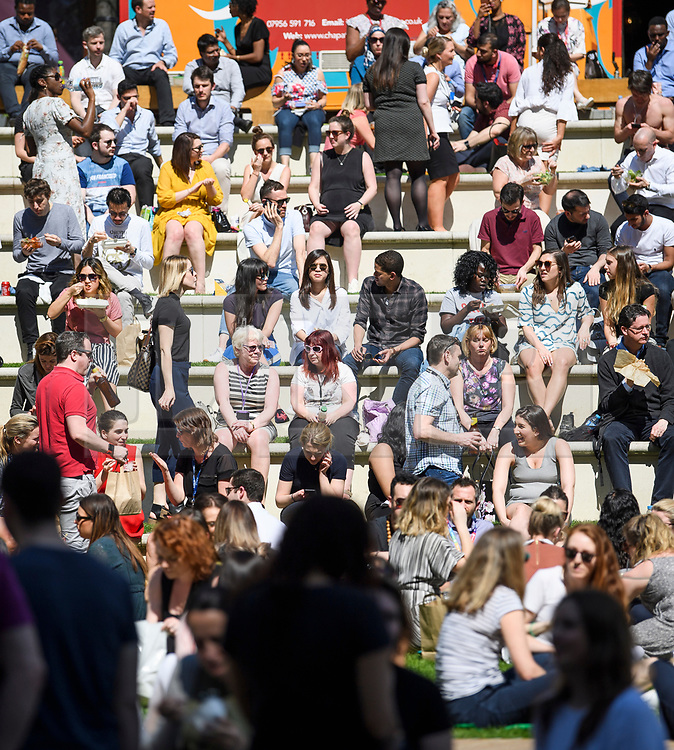 © Licensed to London News Pictures. 19/04/2018. London, UK. Members of the public gather for lunch in the sunshine at Paddington Basin in West London as parts of the UK are enjoying high unseasonal April temperatures. Photo credit: Ben Cawthra/LNP