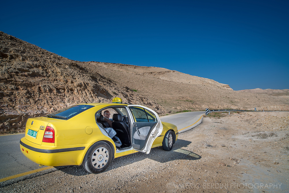 The driver of a Palestinian taxi, allowed to work only within the West Bank. The green plates are forbidden to cross Israeli checkpoints. All Palestinian taxis are yellow to differentiate from the Israeli ones, which are white. Israeli taxis are allowed to travel everywhere. Taxis are the best way to travel around West Bank, taxist know places and can be fantastic touristic guides.