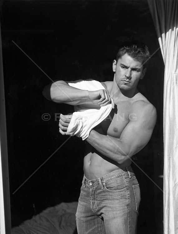 handsome man at home putting on a tee shirt while looking out a glass window
