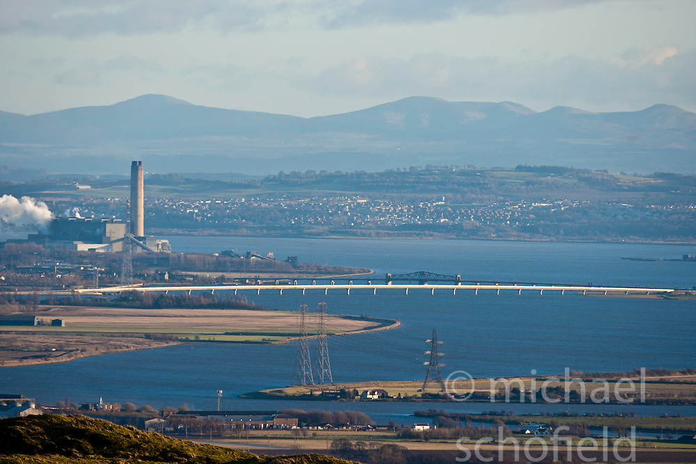 Longannet power station, the large coal-fired power station in Fife, with the Clackmannanshire Bridge road bridge over the Firth of Forth. with the swinging central section of Kincardine Bridge behind. View from the slope of the Dumyat, a hill at the western extremity of the Ochil Hills, in central Scotland..Pic © Michael Schofield...