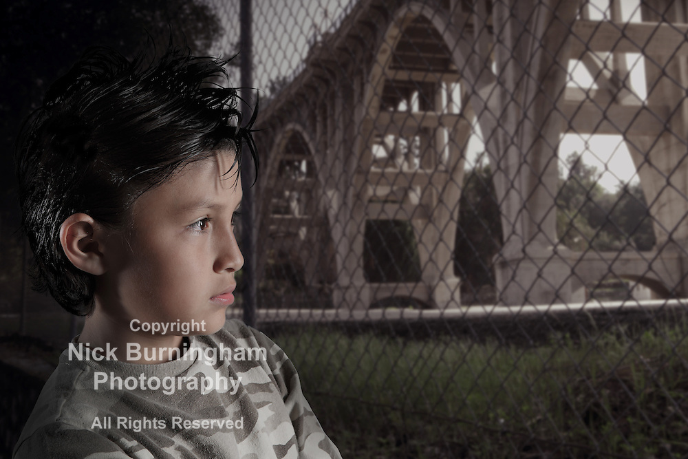 Boy in an urban environment with dramatic lighting and desaturated colors with bridge in background - EXCLUSIVELY AVAILABLE HERE and ALAMY