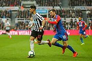 Ayoze Perez (#17) of Newcastle United dribbles the ball towards the penalty area pursued by James McArthur (#18) of Crystal Palace during the Premier League match between Newcastle United and Crystal Palace at St. James's Park, Newcastle, England on 6 April 2019.
