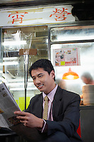 Young business man reading newspaper in bar