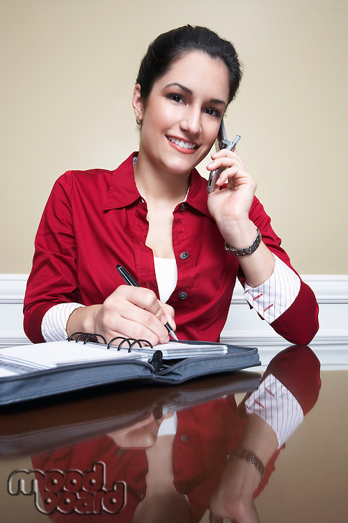 Business woman using mobile phone and writing in diary in office, portrait