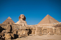 The Giza ruins with the Sphinx and 2 pyramids against a clear, blue sky.