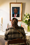 Brussels Belgium 6th December 2013. At the South African Embassy in Brussels people gather. Nelson Mandela died just yesterday.woman signs the book in front of Mandela's portrait