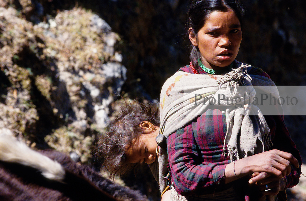 Kalikot, 06 March 2005... A mother carries her child on her back while she works.