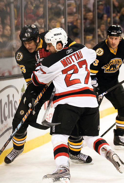 29 January 2009: Devils defensemen Mike Mottau #27 checks Bruins forward Blake Wheeler #26 into the boards during the New Jersey Devils 4-3 win over the Boston Bruins at the TD Banknorth Garden in Boston, MA.*****Editorial Usage Only*****