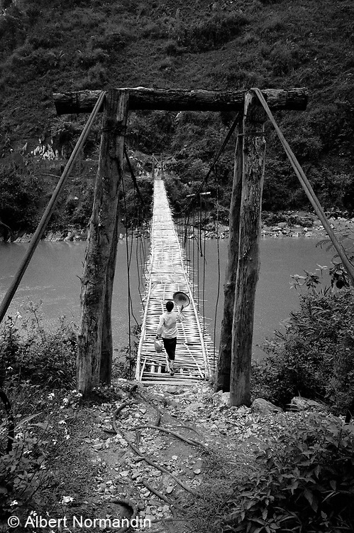 Woman with hat crossing bamboo suspension bridge