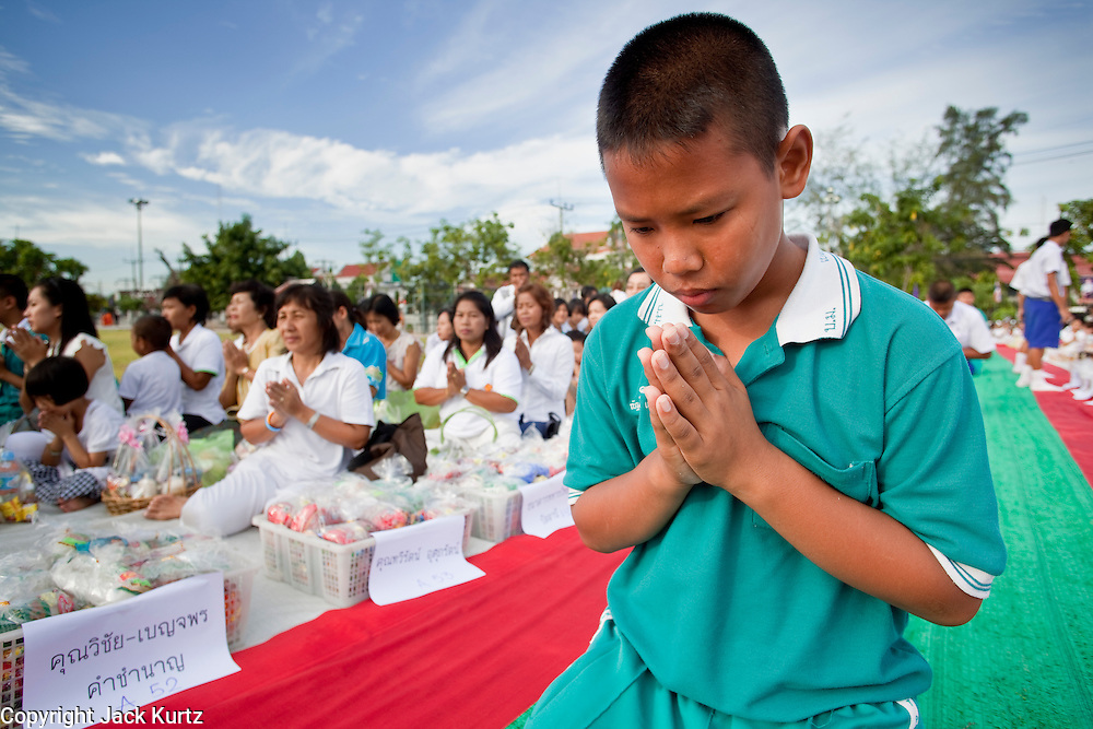 """Sept. 26, 2009 -- PATTANI, THAILAND: Thai school children pray during the Tak Bat Sankatan ceremony in Pattani, Thailand, Saturday. Buddhists in Thailand's three southern most provinces gathered in Pattani Saturday, Sept 26 to celebrate Tak Bat Sankatan, the day Lord Buddha returned to earth and was greeted by a crawd of his disciples and Buddhist believers who were waiting to offer him food. Buddhists monks representing the 266 """"Wats"""" (temples) in the three provinces (Pattani, Narathiwat and Yala) processed through the crowd and were presented with food and gifts.   Photo by Jack Kurtz"""