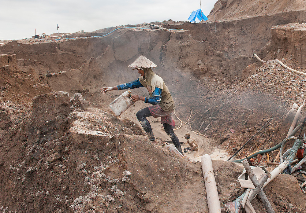 Miner clims with difficulty an unstable sand ridge in a huge illegal tin mine in Batako, Tunghin, that has completely devastated the once green landscape. Bangka Island (Indonesia) is devastated by a deadly tin rush, a direct consequence of the success of smartphones and tablets like iPhones and iPads from Apple or Samsung. The demand and price for tin has increased due to its use in smart phones and tablets. <br /> <br /> <br /> Mineur monte avec difficult&eacute; une cr&ecirc;te de sable instable dans une mine d'&eacute;tain ill&eacute;gale &agrave; Batako - Tunghin, qui a compl&egrave;tement d&eacute;vast&eacute; un paysage qui &eacute;tait autrefois verte. L'&icirc;le de Bangka (Indon&eacute;sie) est d&eacute;vast&eacute;e par des mines d'&eacute;tain sauvages, une cons&eacute;quence directe du succ&egrave;s des smartphones et tablettes comme les iPhones et les iPads d'Apple ou Samsung. La demande de l'&eacute;tain a explos&eacute; &agrave; cause de son utilisation dans les smartphones et tablettes.