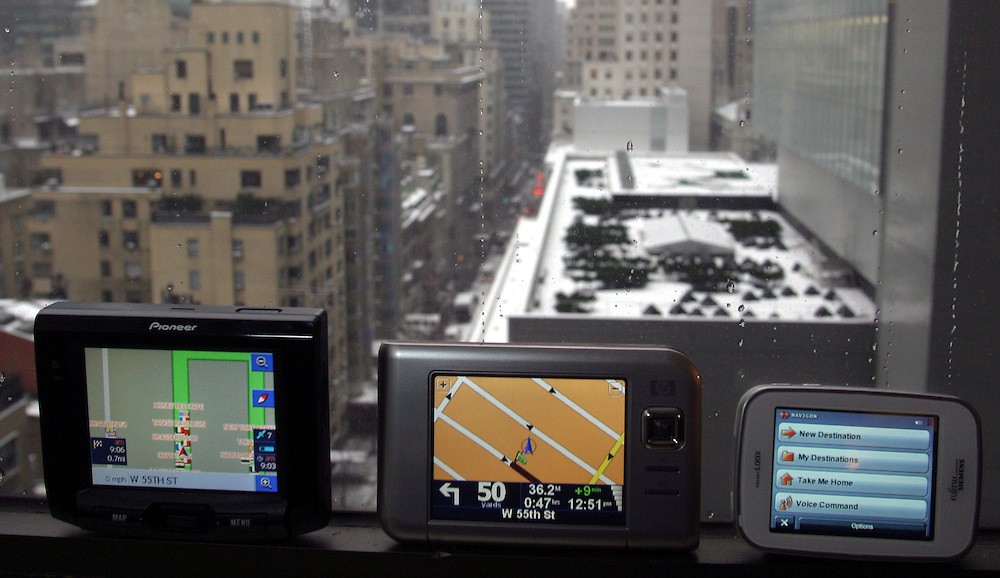 Three New navigator systems next to a window of the Financial Times office in New York  (Black one: Pioneer AVIC-S1, Big Gray: HP Travel Companion, Small gray: Fujitsu Siemens Pocket LOOX)..At   Thursday  February 14 2007.....