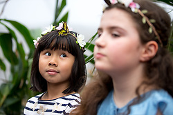 © Licensed to London News Pictures. 28/03/2018. London, UK. A butterfly lands on the head of Ruhi Samir, aged 8 (left) pictured next to Freya Gordon, aged 10 (right) at the 'Sensational Butterflies' exhibition at the Natural History Museum, returning for it's tenth year. Photo credit : Tom Nicholson/LNP