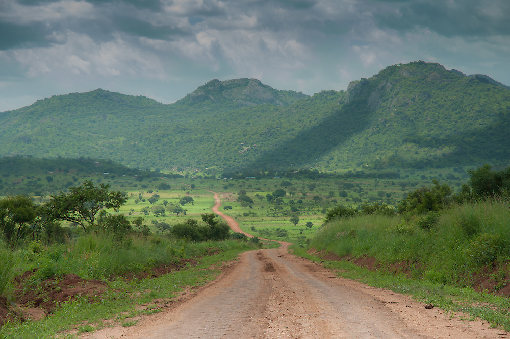 Road to Kidepo National park with on the background the mountains on the border with South-Sudan, Kidepo National park, Uganda.