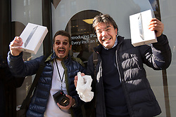 © licensed to London News Pictures. London, UK 02/11/2012. Two new iPad owners posing with their tablets outside Apple Store on Regent Street, London as highly anticipated tablet meets the costumers on 02/11/12. Photo credit: Tolga Akmen/LNP